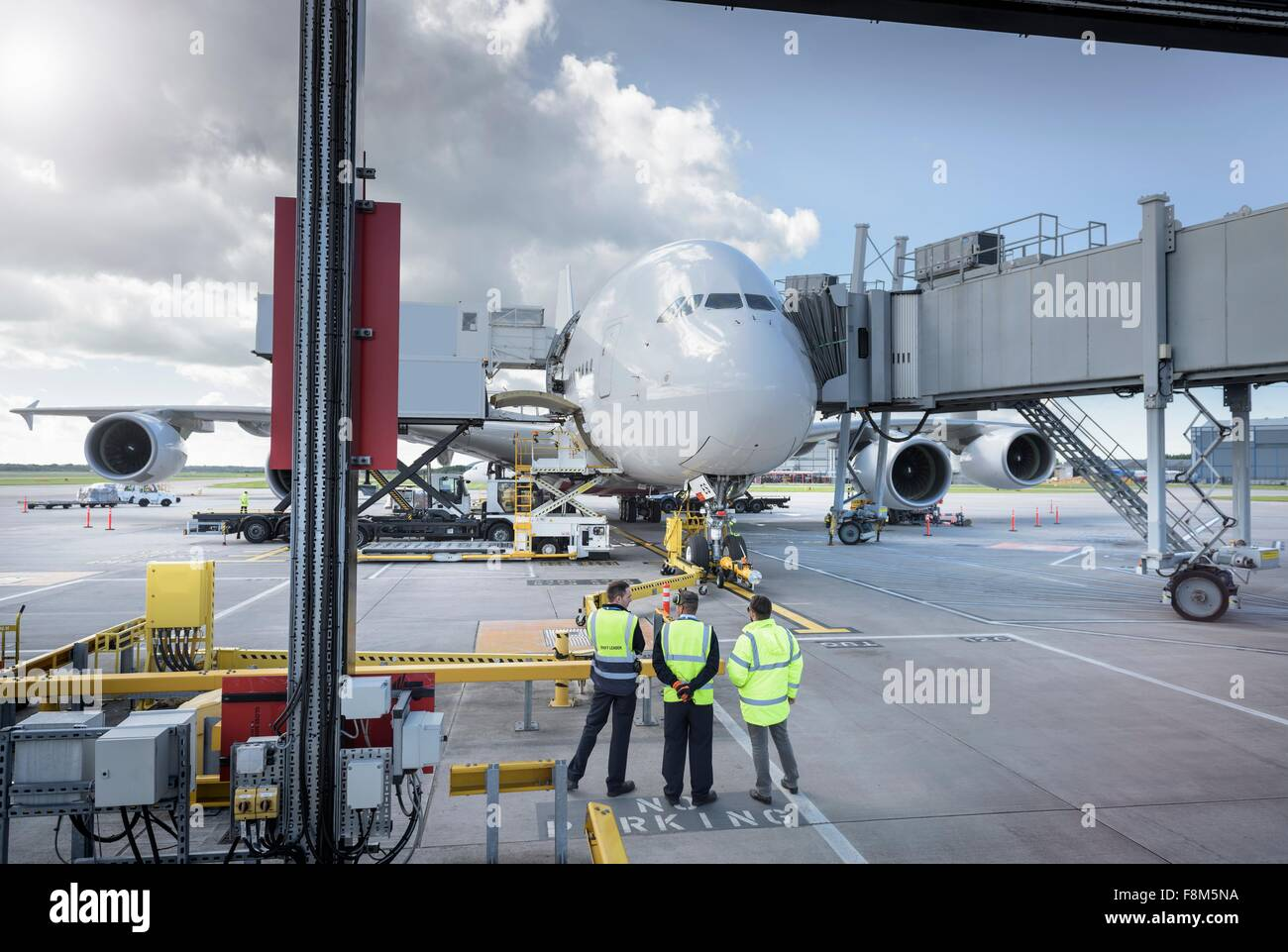 Ground crew inspecting A380 aircraft on stand in airport - Stock Image