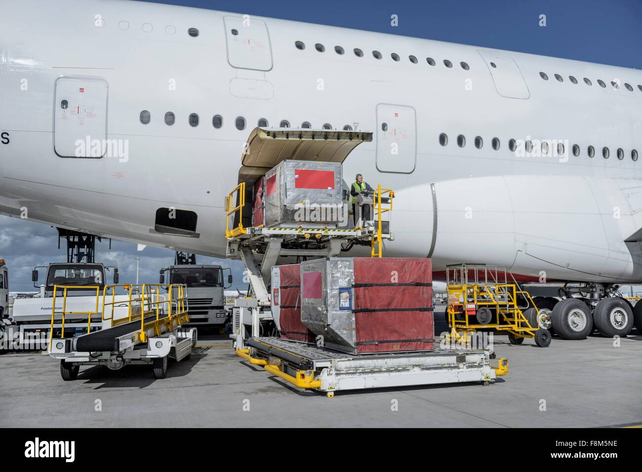 Ground crew loading freight and luggage into A380 aircraft - Stock Image