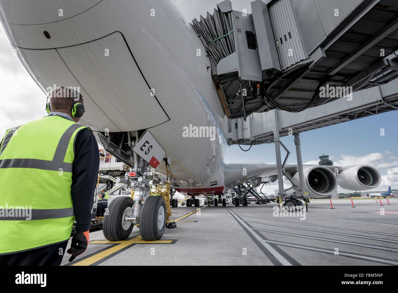 Engineer inspecting A380 aircraft at stand in airport - Stock Image