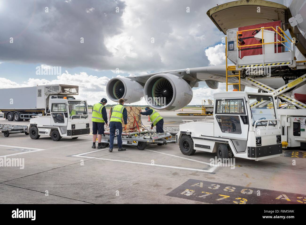 Ground crew loading freight onto A380 aircraft - Stock Image