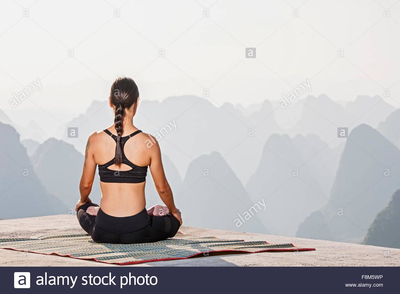 Rear view of woman in yoga lotus pose above limestone mountains, Yangshuo, Guangxi Zhuang, China - Stock Image