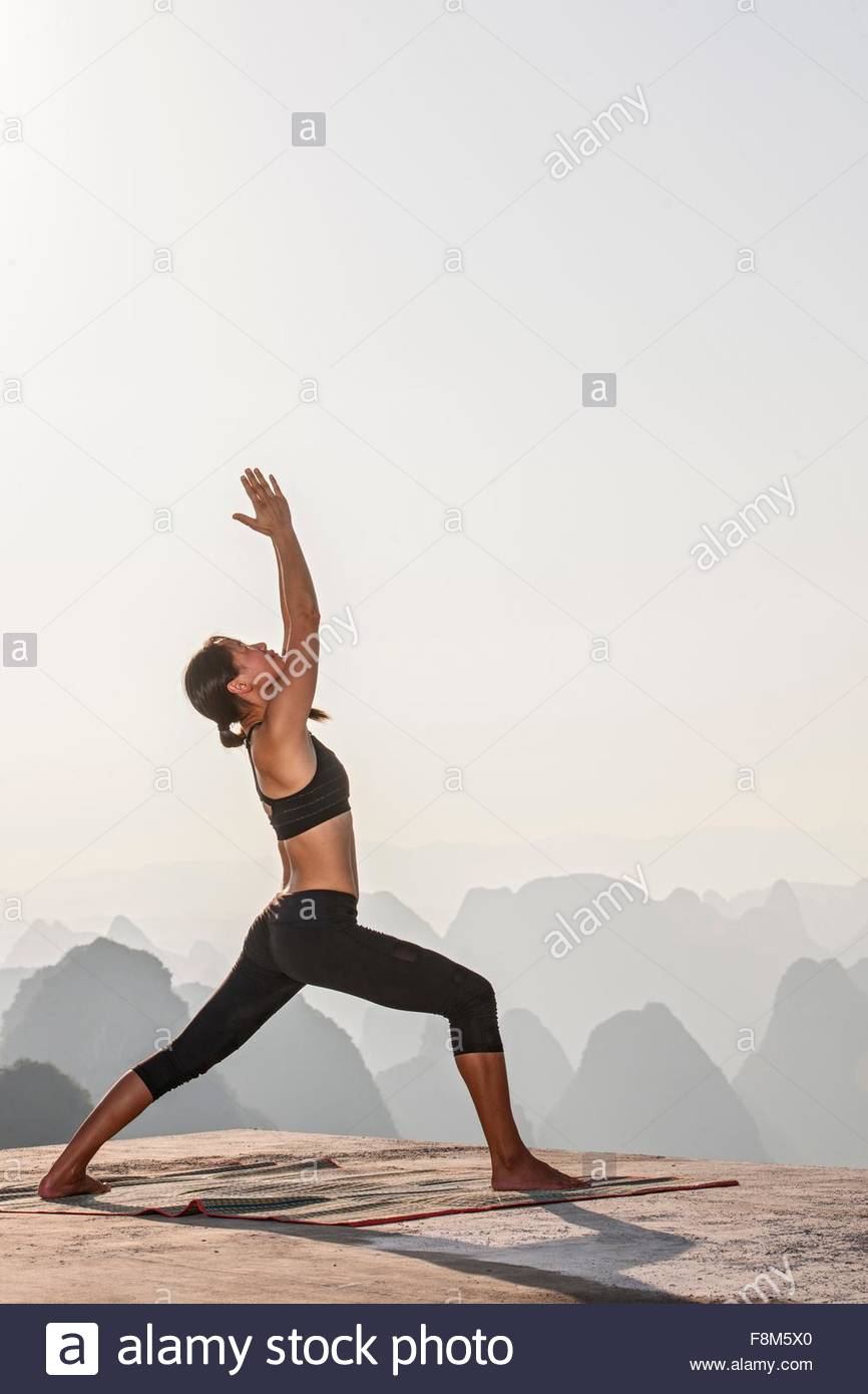 Side view of woman in yoga warrior pose above limestone mountains, Yangshuo, Guangxi Zhuang, China - Stock Image