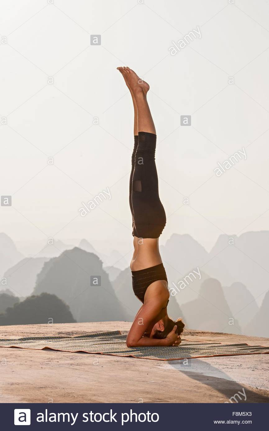 Side view of woman in headstand yoga pose above limestone mountains, Yangshuo, Guangxi Zhuang, China - Stock Image