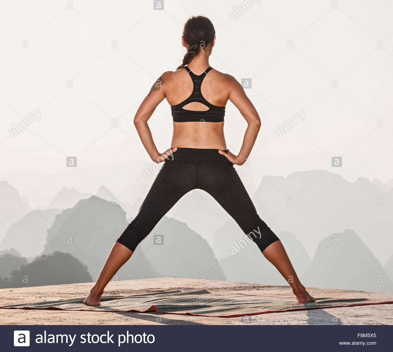 Rear view of woman in yoga pose above limestone mountains, Yangshuo, Guangxi Zhuang, China - Stock Image