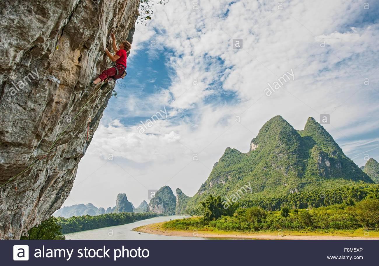 Side view of male climber at Riverside crag in Yangshuo, Guangxi Zhuang, China - Stock Image