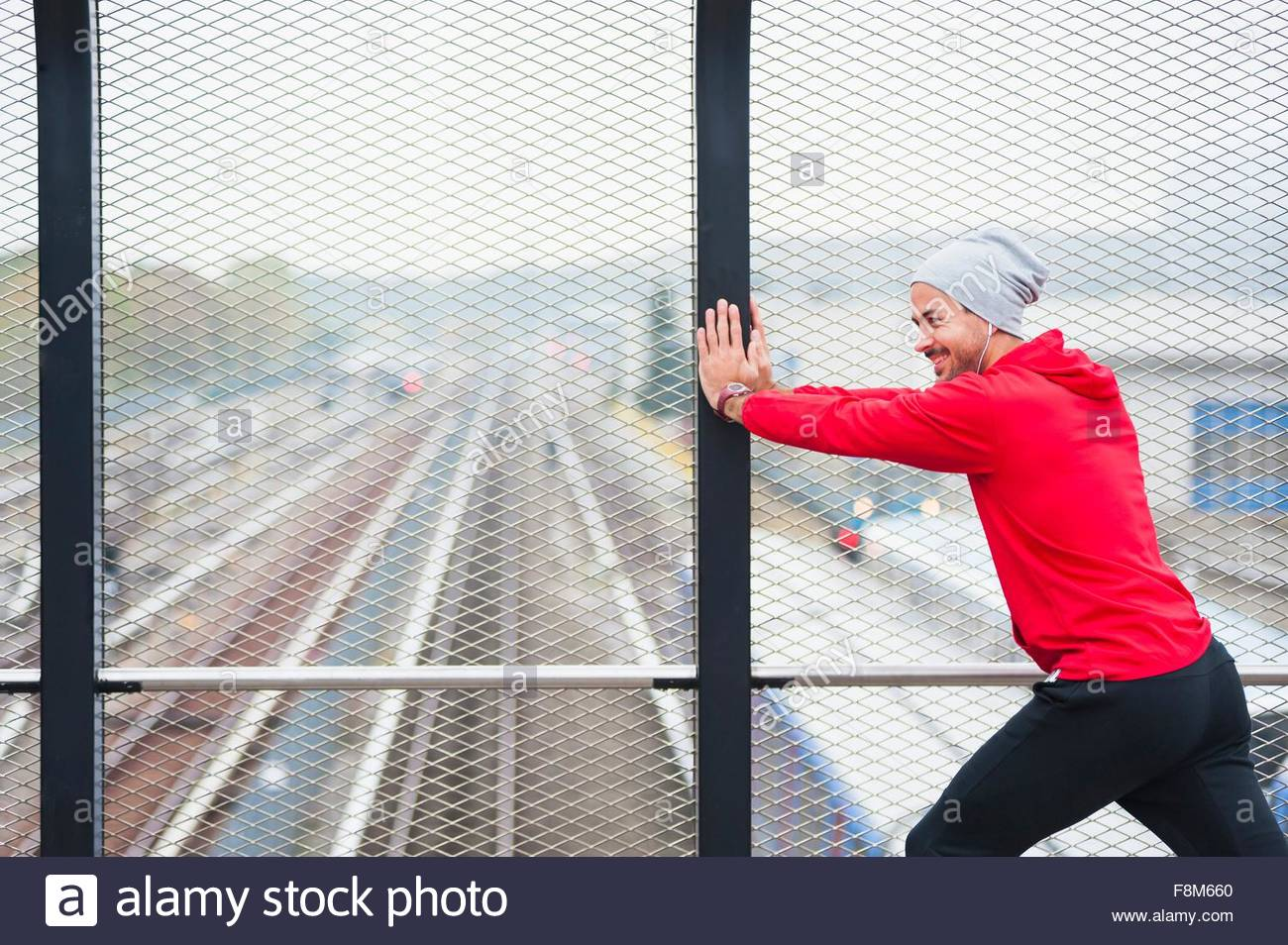Young man doing physical training on city footbridge - Stock Image