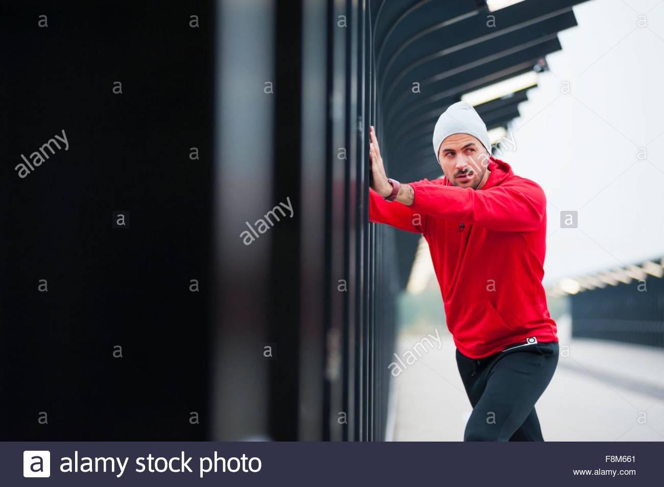 Young man doing physical push training on city footbridge - Stock Image