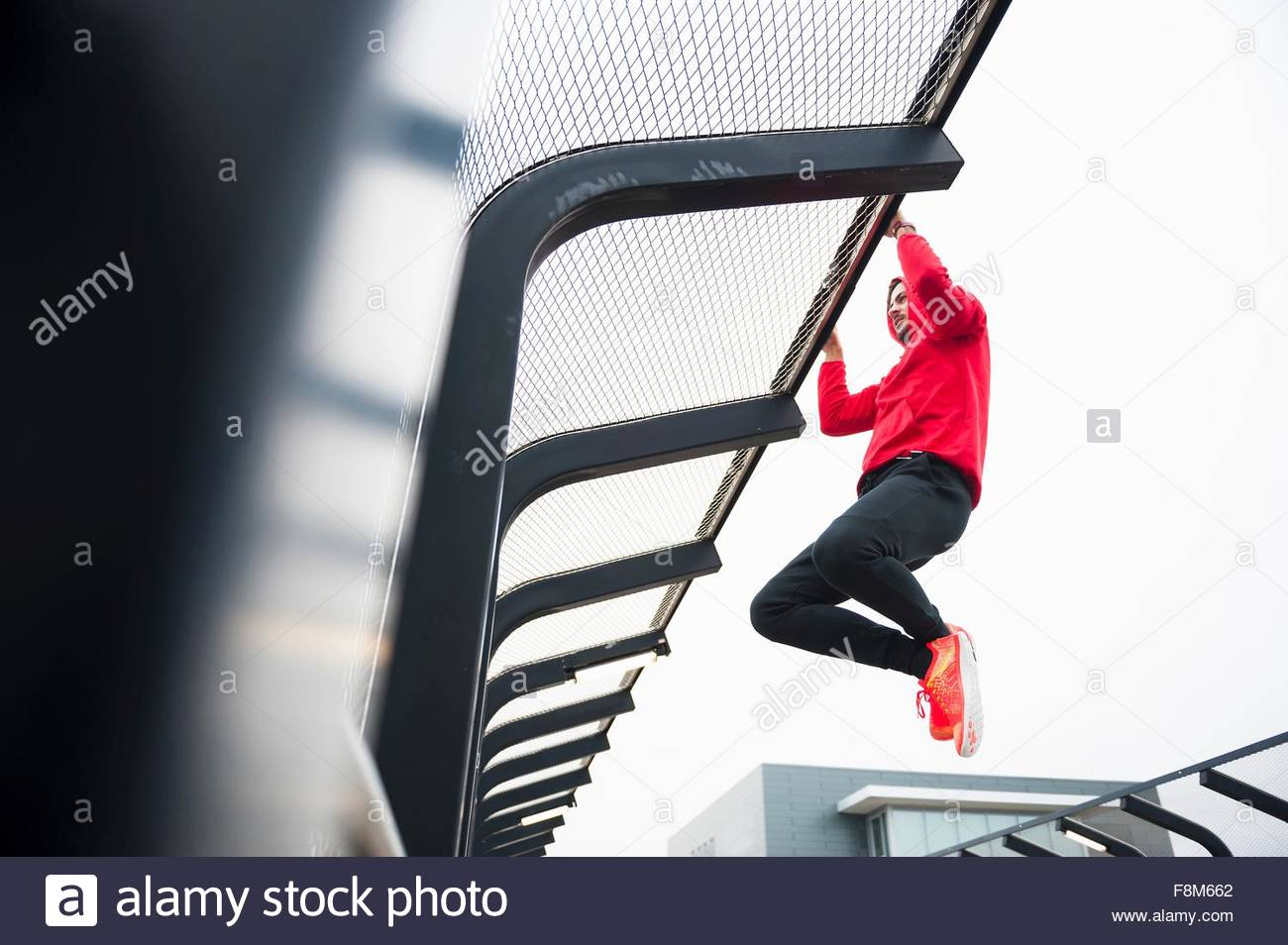 Low angle view of young man doing pull up training on city footbridge - Stock Image