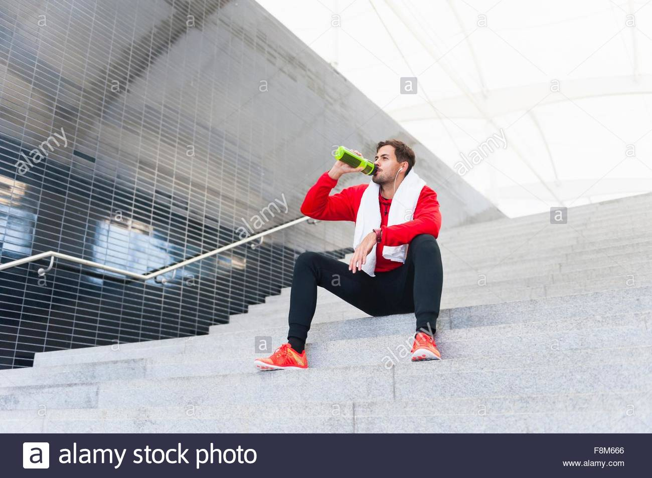 Young male runner drinking water bottle on city stairway - Stock Image