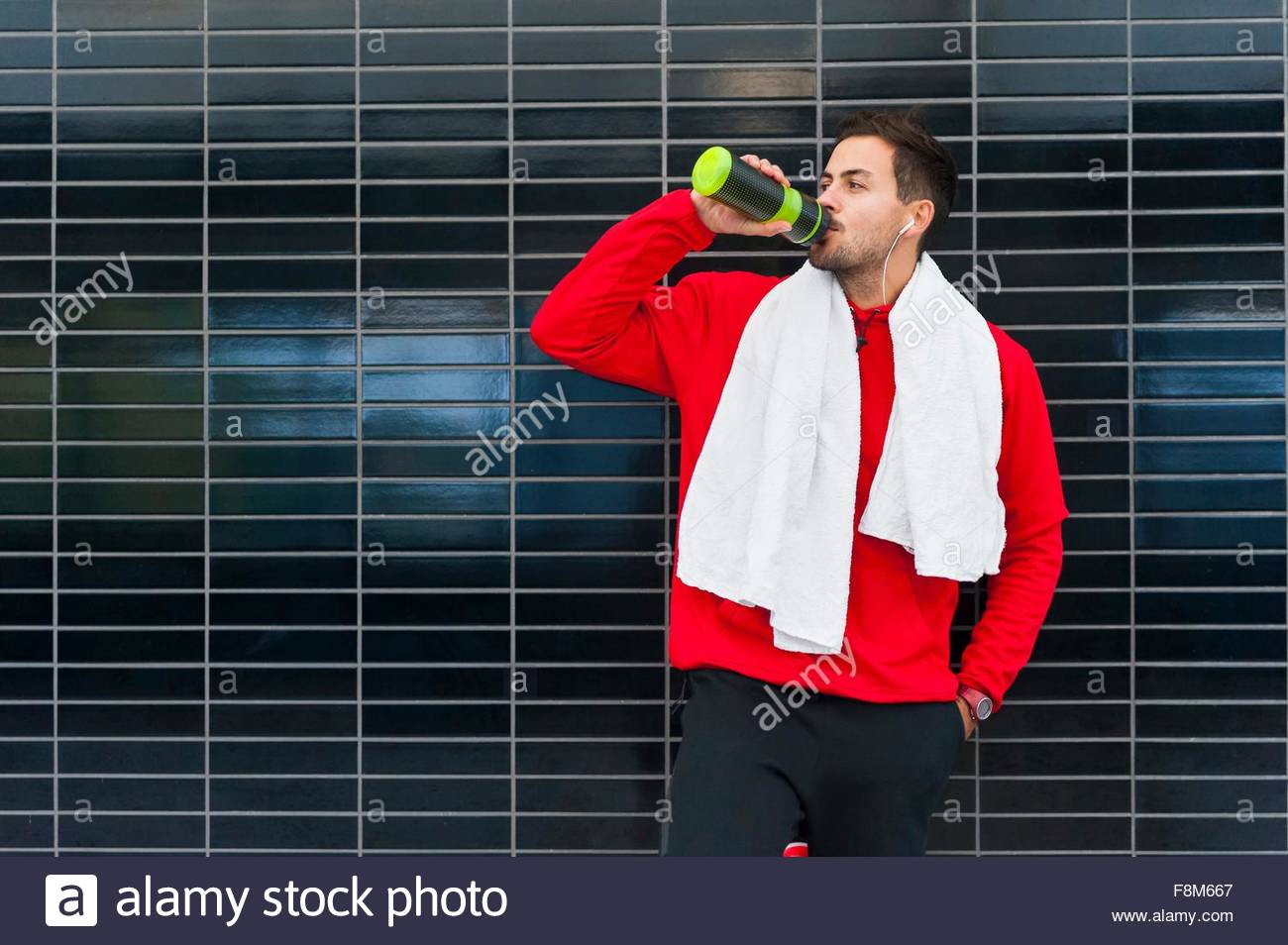 Young male runner leaning against tiled wall drinking water - Stock Image