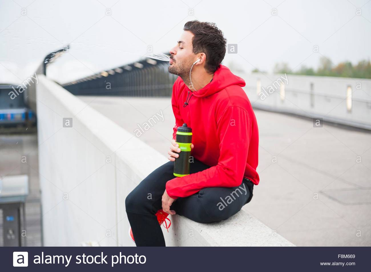 Young male runner sitting on rooftop edge with water bottle - Stock Image