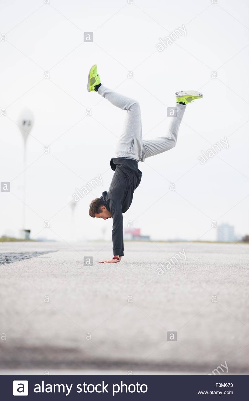 Young male runner doing handstand in sport arena - Stock Image