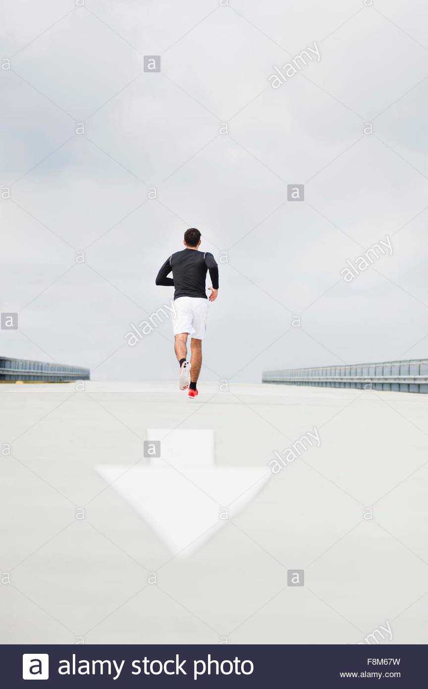 Rear view of young male runner running on parking lot roof - Stock Image