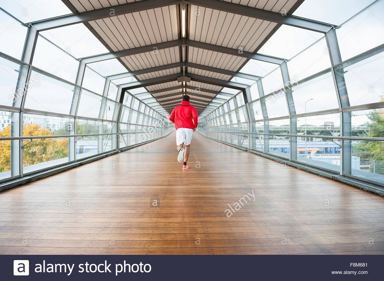 Rear view of young male runner running across footbridge - Stock Image