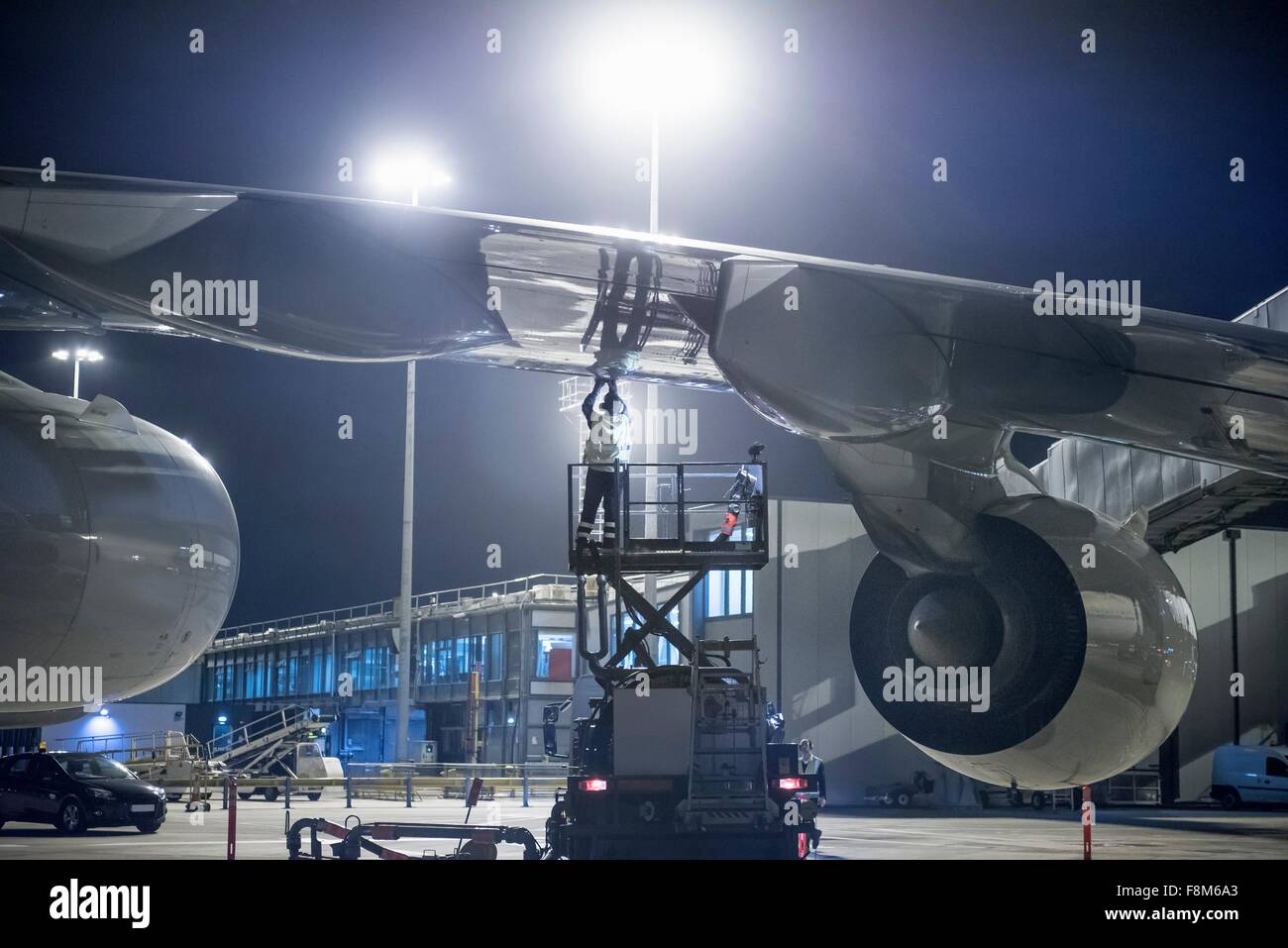 Ground crew member refuelling A380 aircraft at night - Stock Image