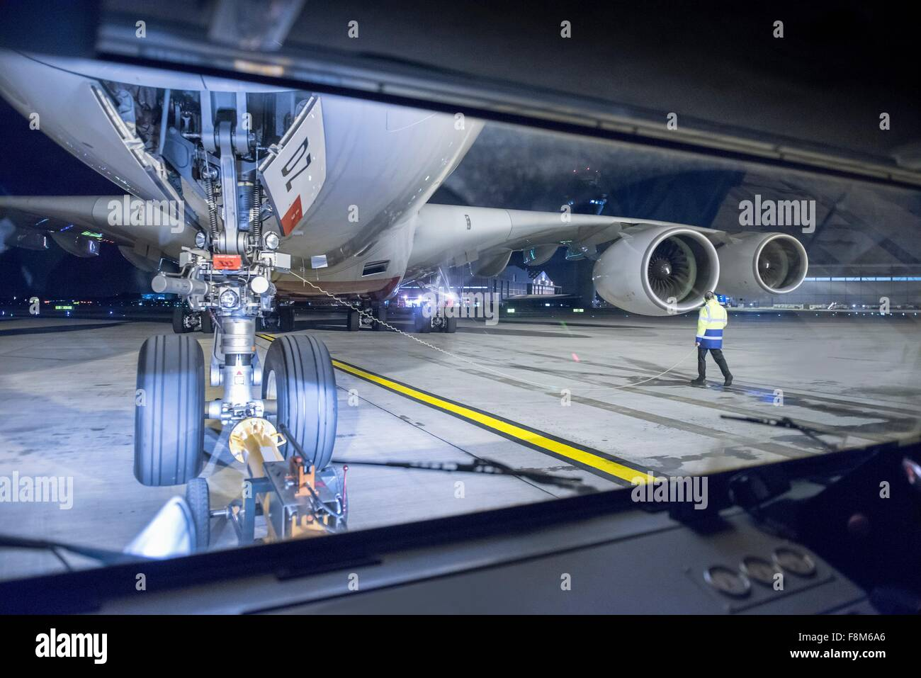 View of A380 aircraft on runway from tug at night - Stock Image