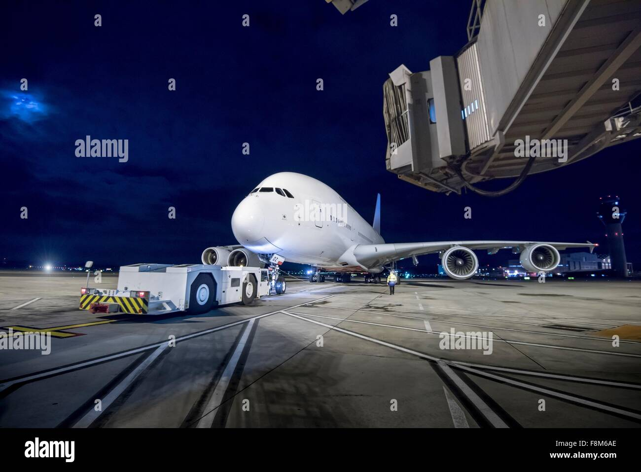 Chief engineer with A380 aircraft on runway at night - Stock Image