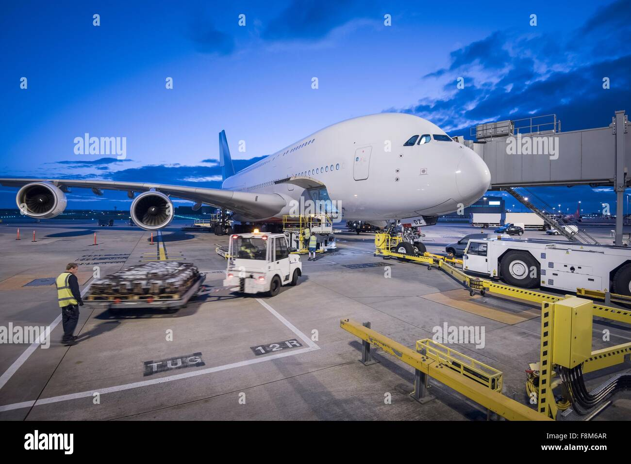 Ground crew attach tug to A380 aircraft on stand at dusk at airport - Stock Image