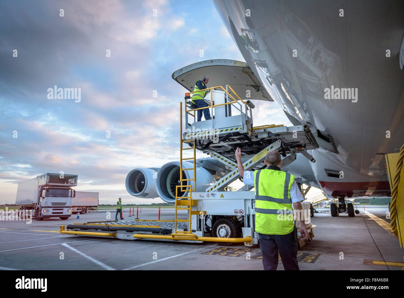 Ground crew attending to A380 aircraft with freight loader at airport - Stock Image