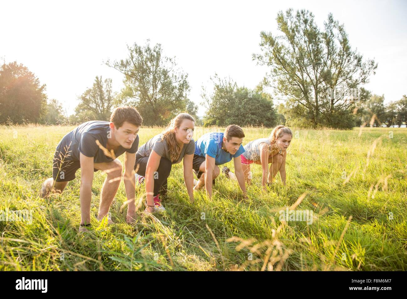 Group of friends in field, in starting position, about to race - Stock Image