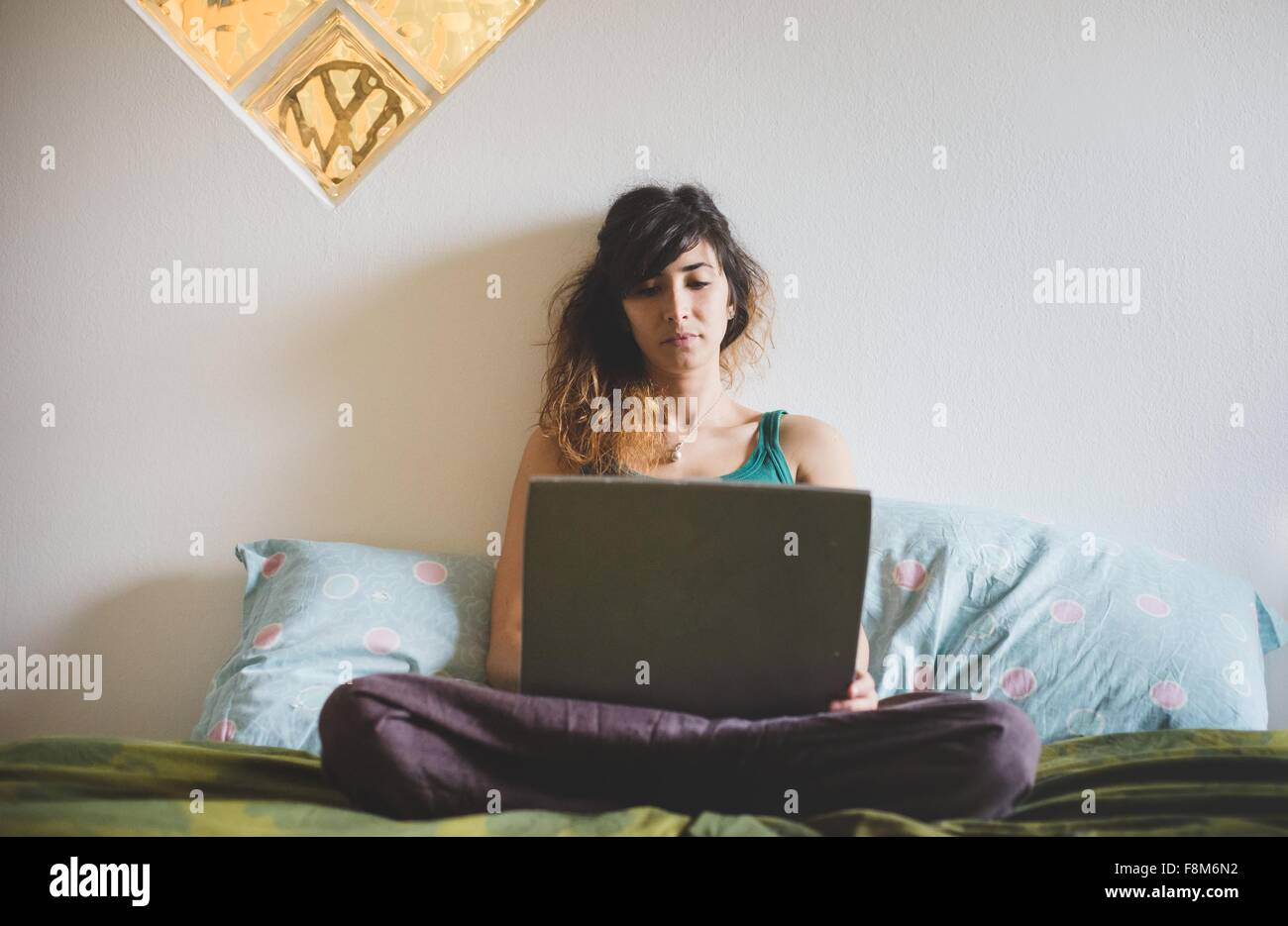 Front view of mid adult woman sitting cross legged on bed using laptop computer - Stock Image
