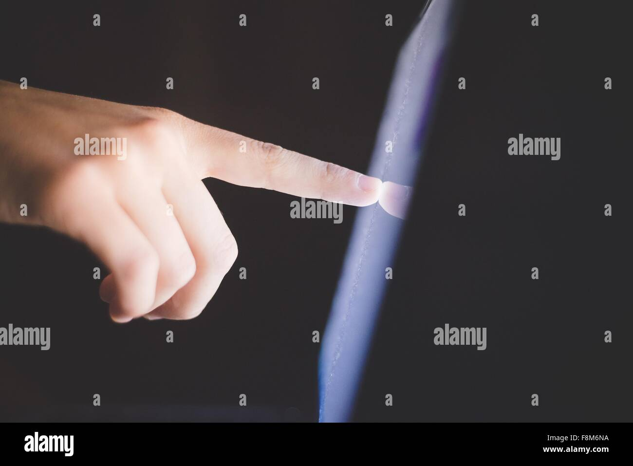 Side view of hand pointing at computer screen - Stock Image