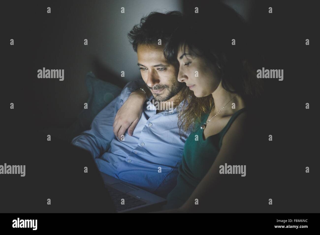 Young woman sitting with arm around young man illuminated by laptop computer screen - Stock Image