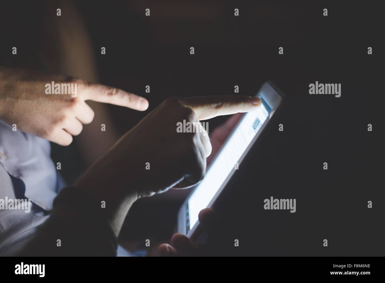 Side view of hands pointing at computer screen - Stock Image