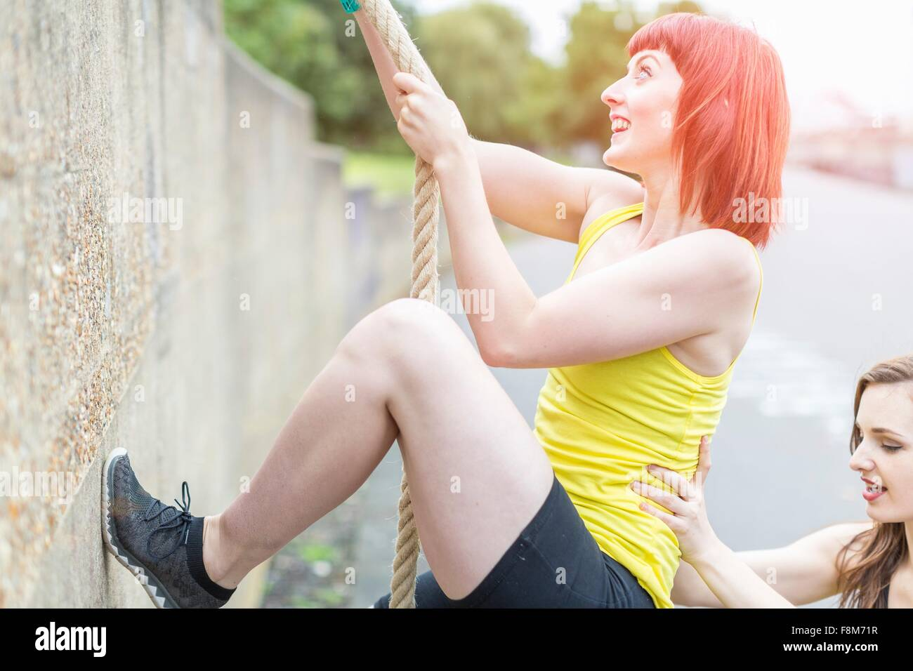 Young women climbing over wall with rope - Stock Image