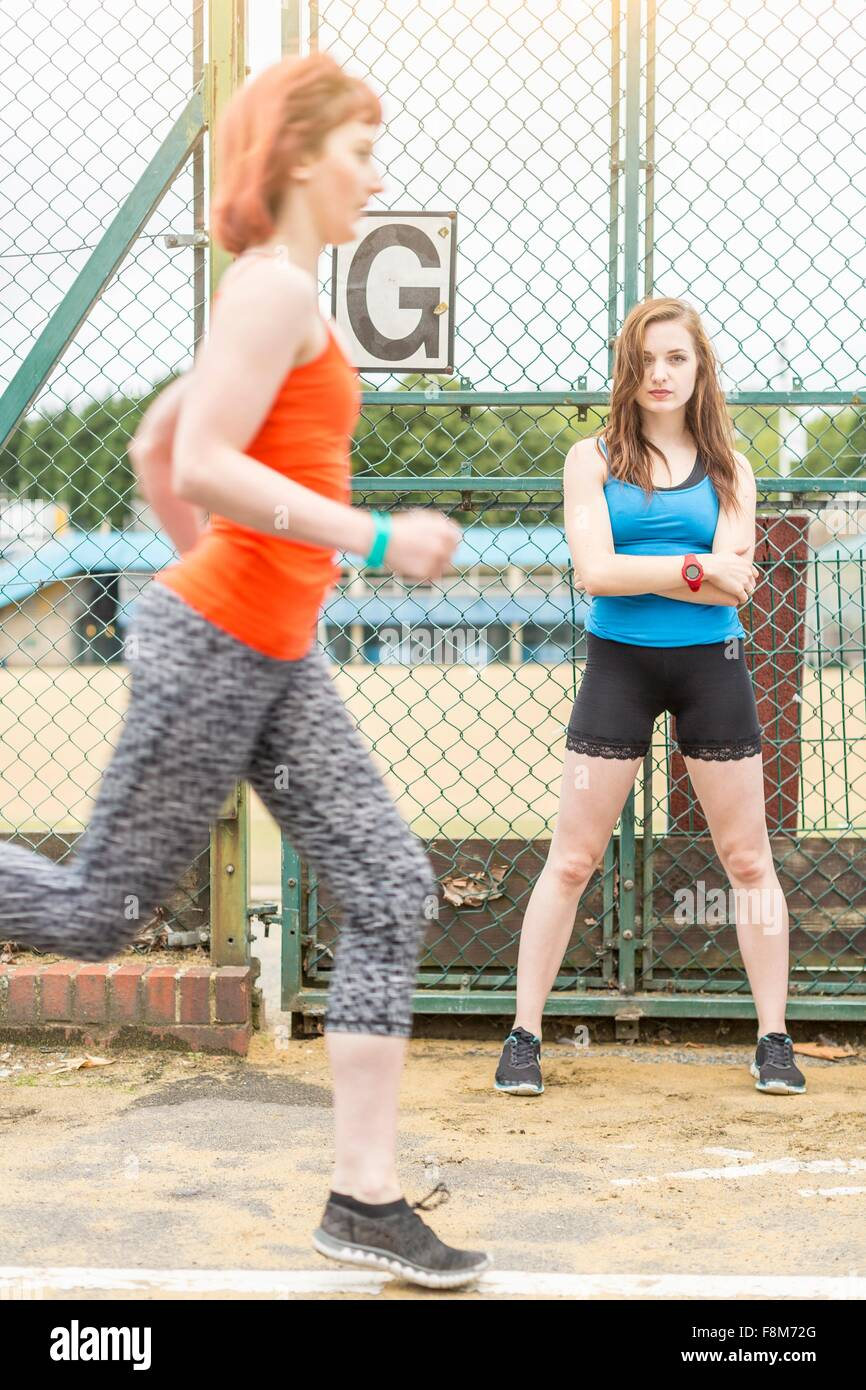 Runner passing young woman standing beside sports ground, London, UK - Stock Image