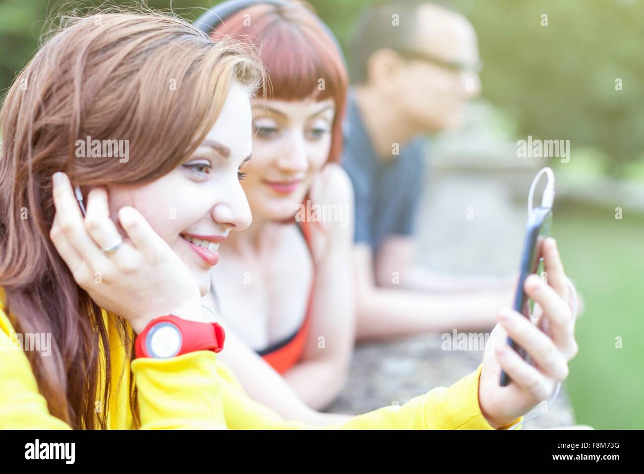 Young women using smartphone, leaning on low wall - Stock Image