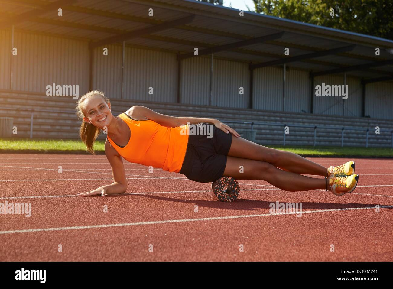 Portrait of young female runner balancing on side at race track - Stock Image