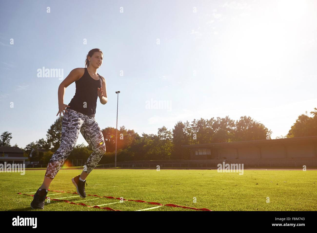 Young woman training on agility ladder on grass - Stock Image