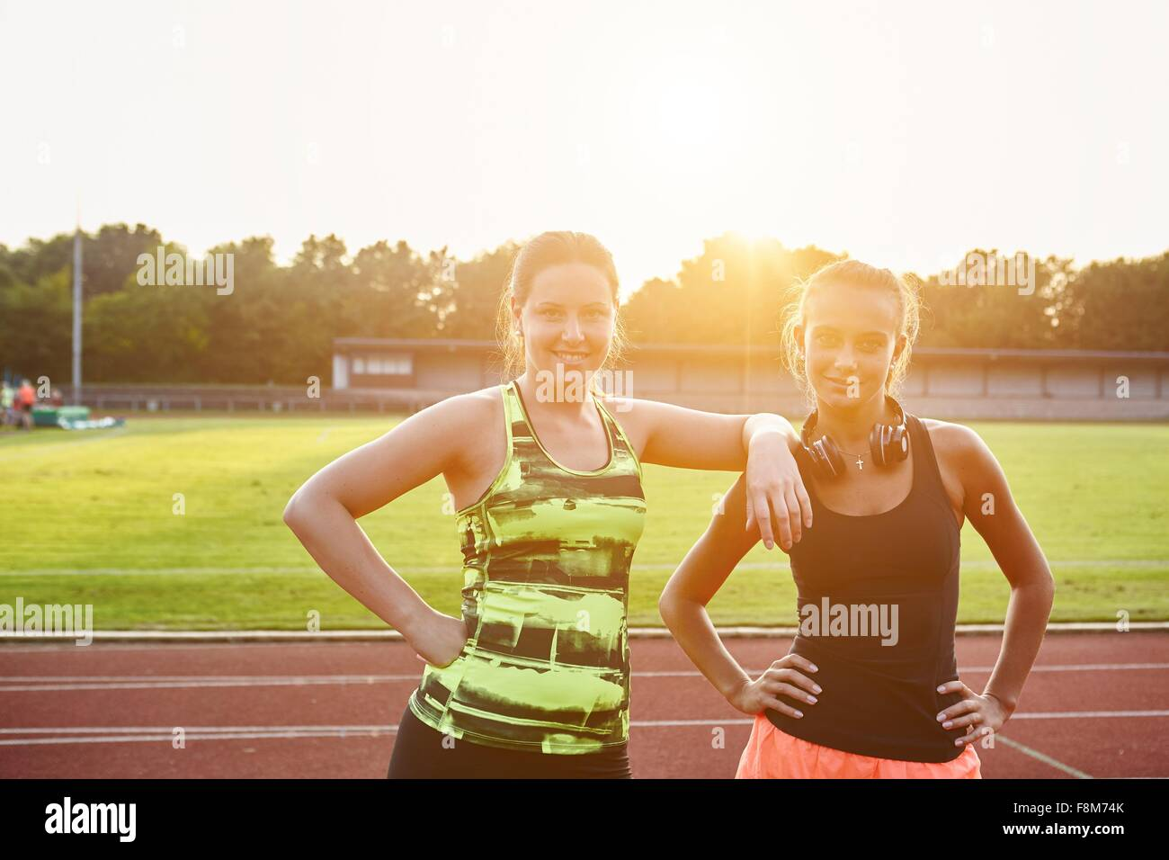 Portrait of two young female runners on race track - Stock Image