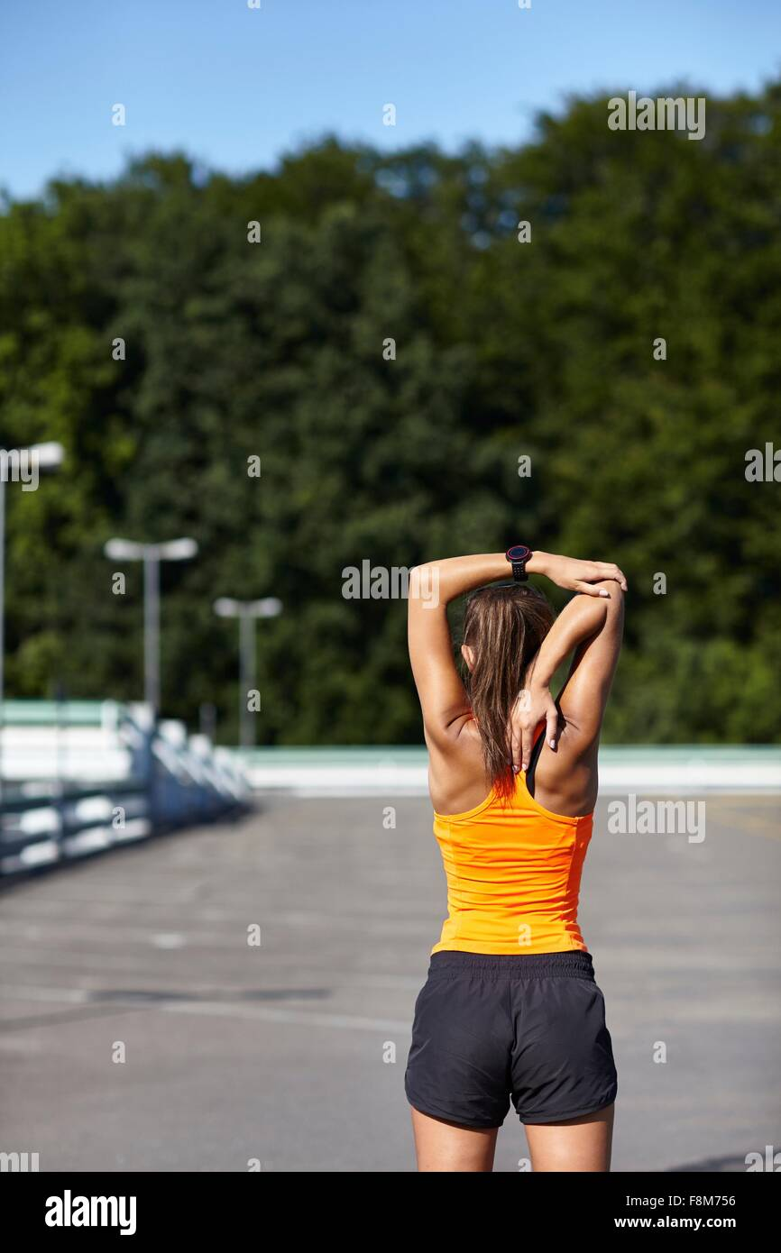 Rear view of young female runner stretching in parking lot - Stock Image