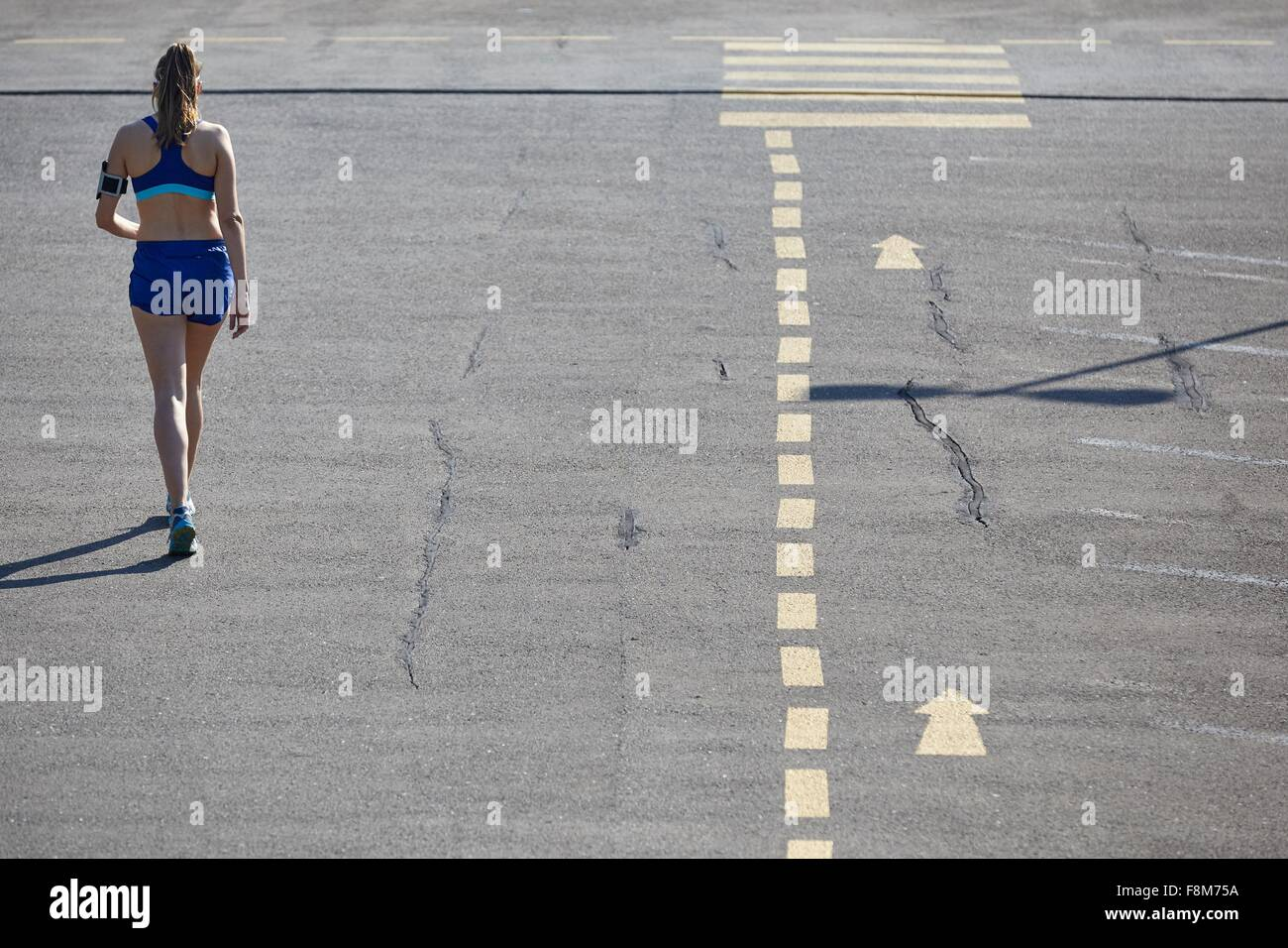 Rear view of young female runner running in parking lot - Stock Image