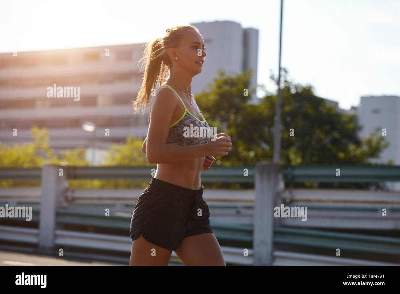 Young female runner running on urban rooftop - Stock Image