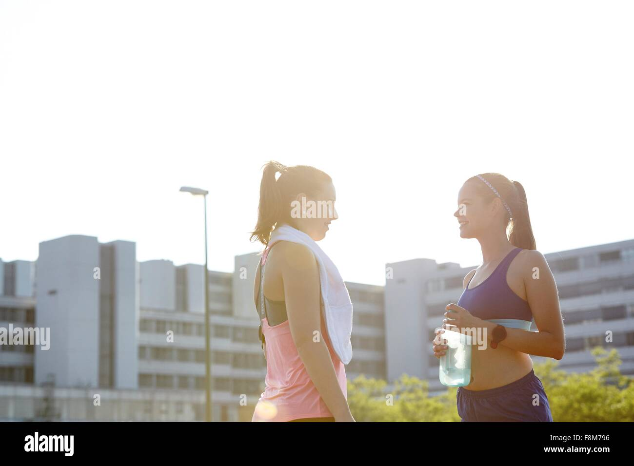 Two young female runners chatting on urban rooftop Stock Photo