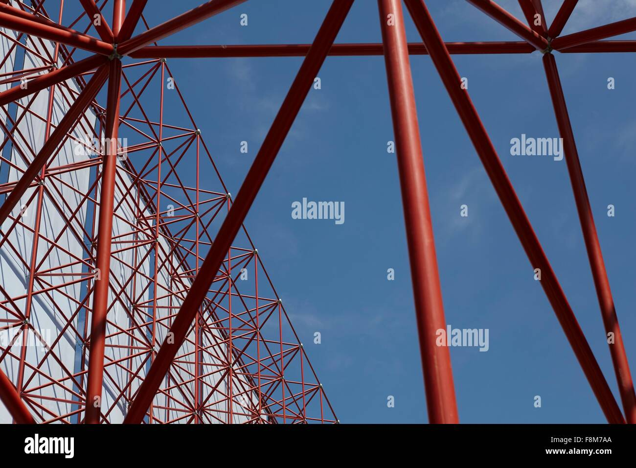 Tall red framework structure with textile against blue sky - Stock Image