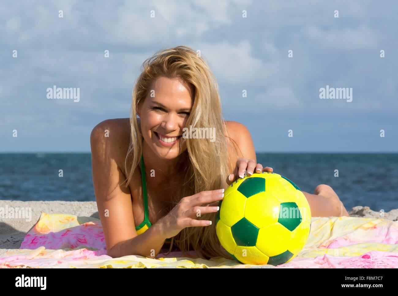 Portrait of woman wearing bikini lying on beach with soccer ball, Miami Beach, Florida, USA - Stock Image