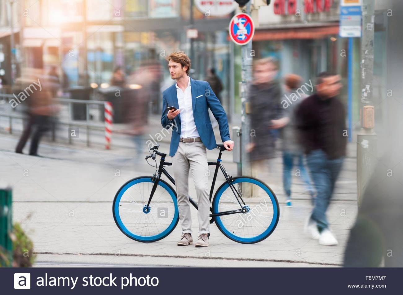 Differential focus of young man with bicycle in busy street holding mobile phone looking away - Stock Image