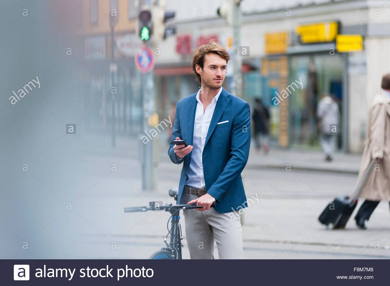 Young man with bicycle in busy street holding mobile phone looking away - Stock Image