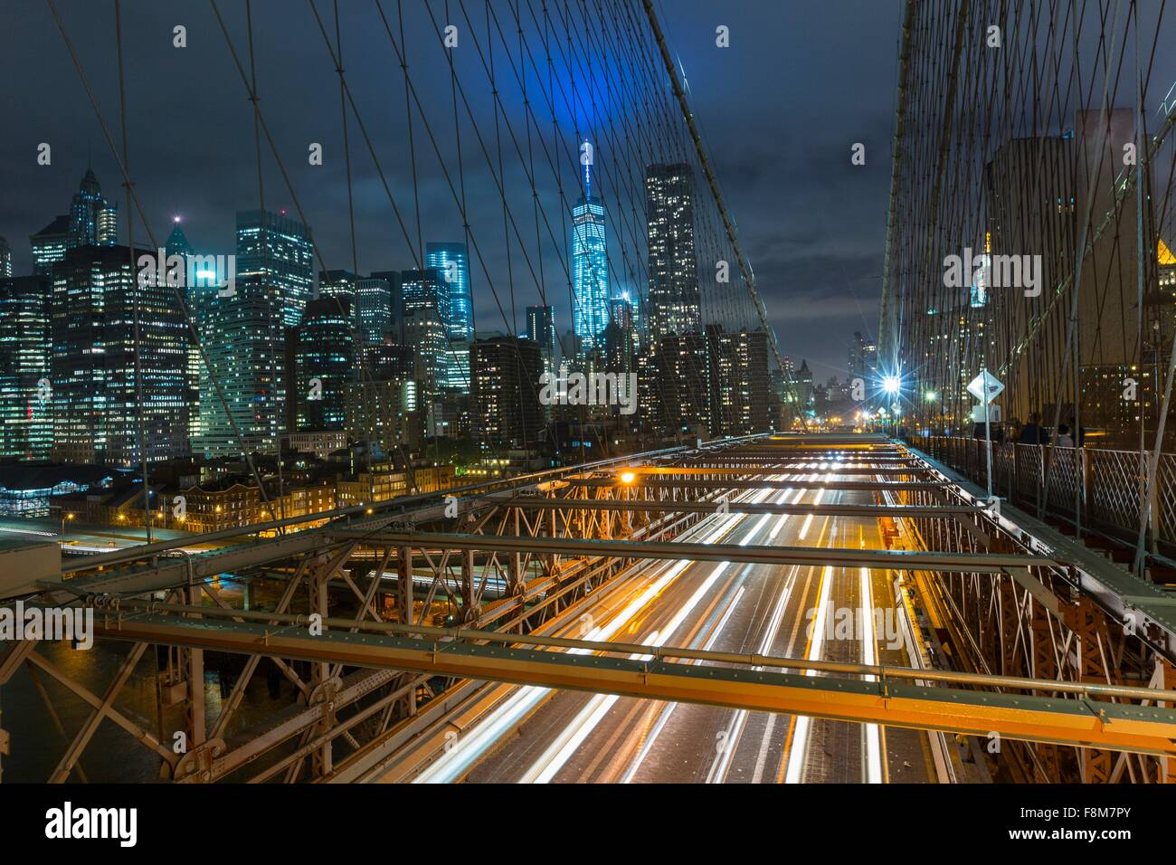 Elevated view of Brooklyn bridge and Manhattan financial district skyline at night, New York, USA - Stock Image