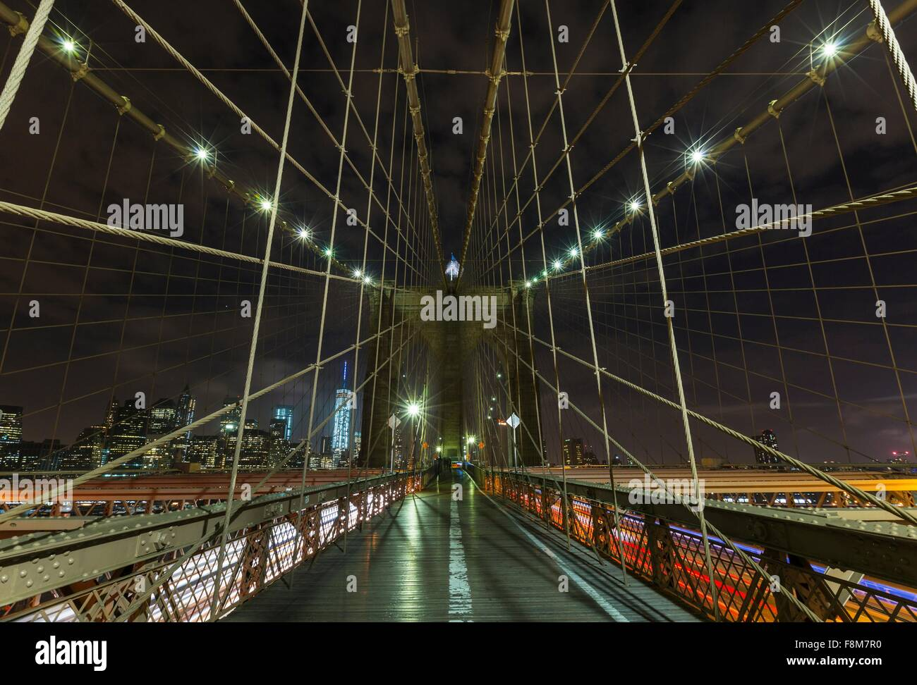 Brooklyn bridge walkway and distant Manhattan financial district skyline at night, New York, USA - Stock Image