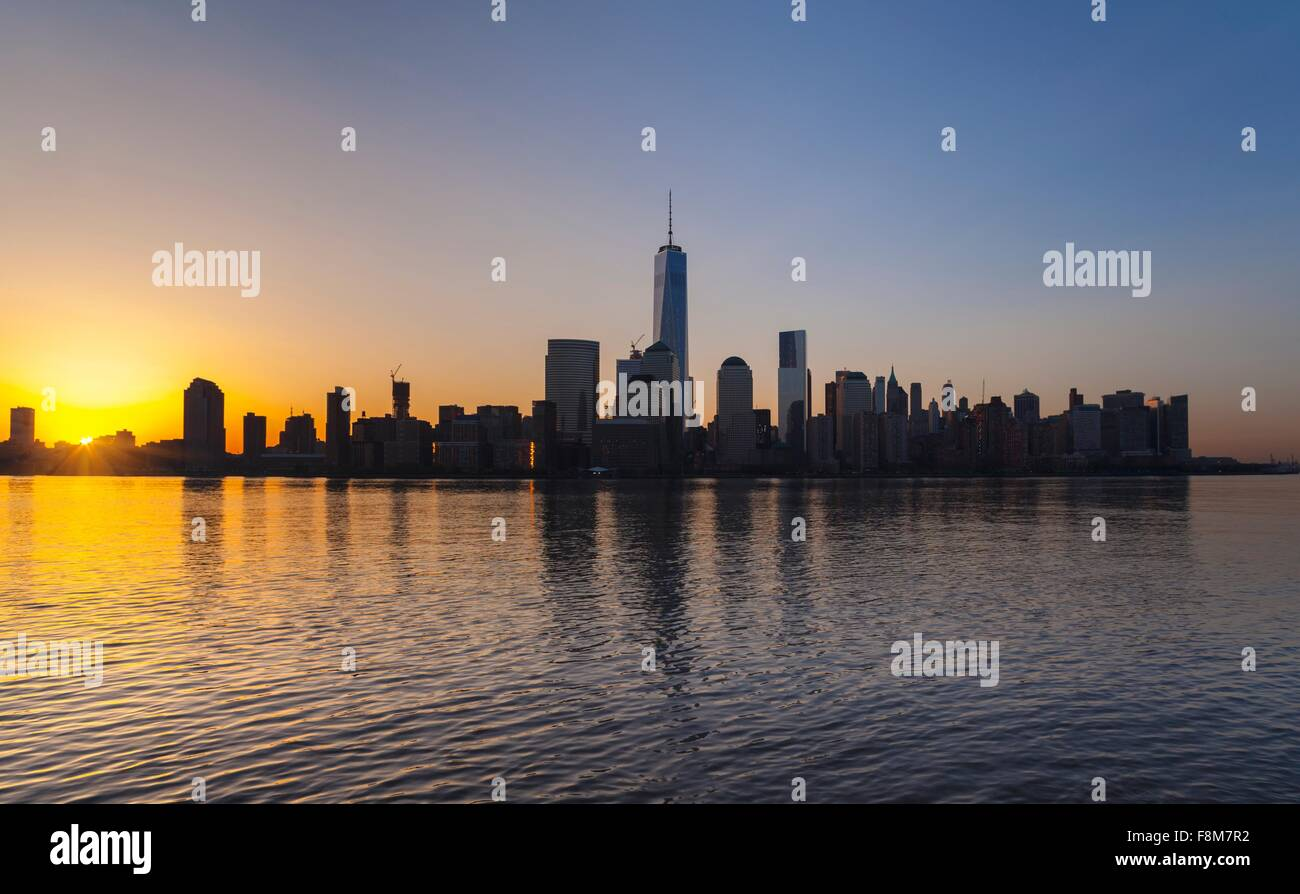 Silhouetted view of Manhattan financial district skyline at sunset, New York, USA - Stock Image