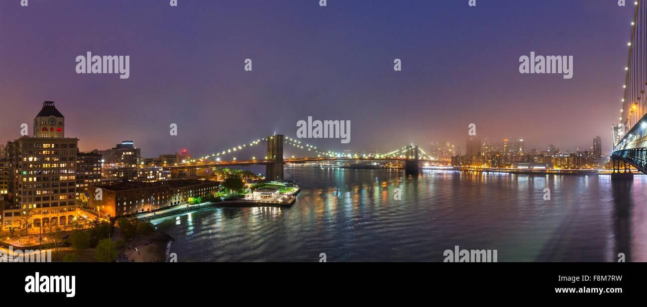Panoramic view of Brooklyn and Manhattan bridges  at night, New York, USA - Stock Image