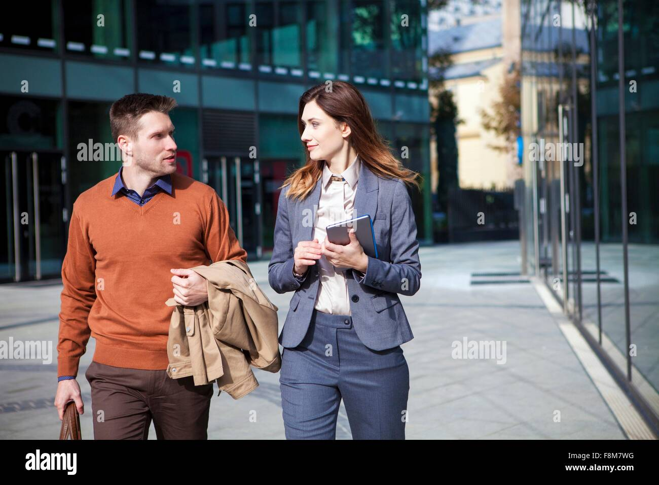 Casual businessman and woman on way to work - Stock Image