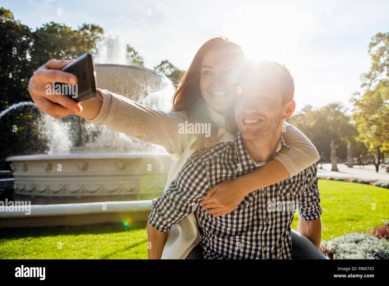 Woman taking selfie having a piggy back in park Stock Photo