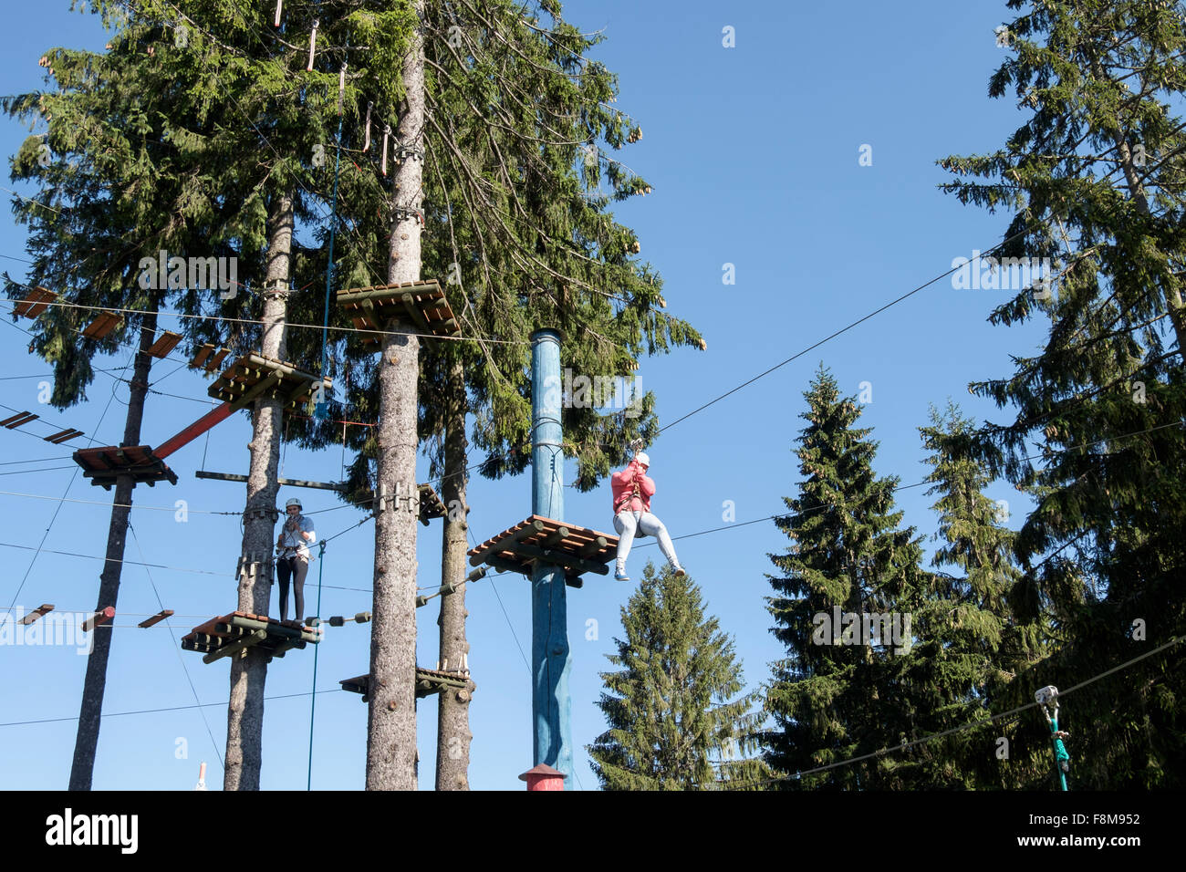 Girl riding on zip wire on Trollandia Highwire Park aerial ropeway and obstacle course. Gubałówka Mountain - Stock Image