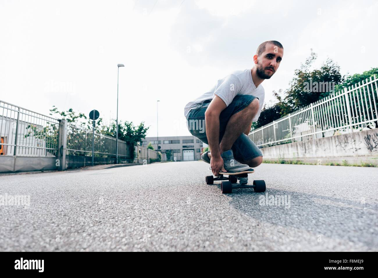 Young man crouched on skateboard Stock Photo
